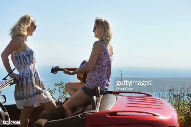 Two woman sat in open top car playing guitar by the sea