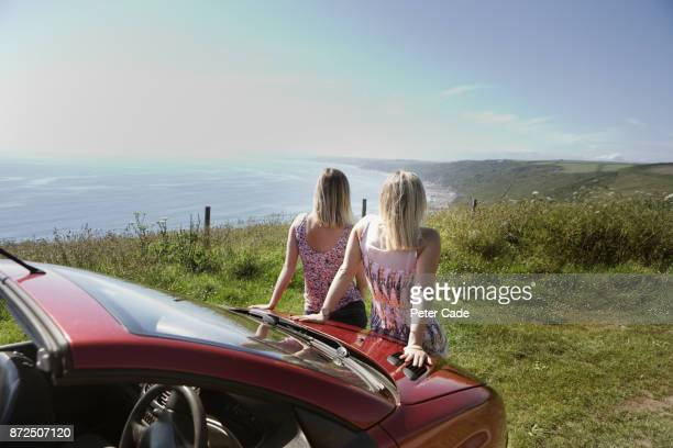 Two woman sat on bonnet of car looking out to sea