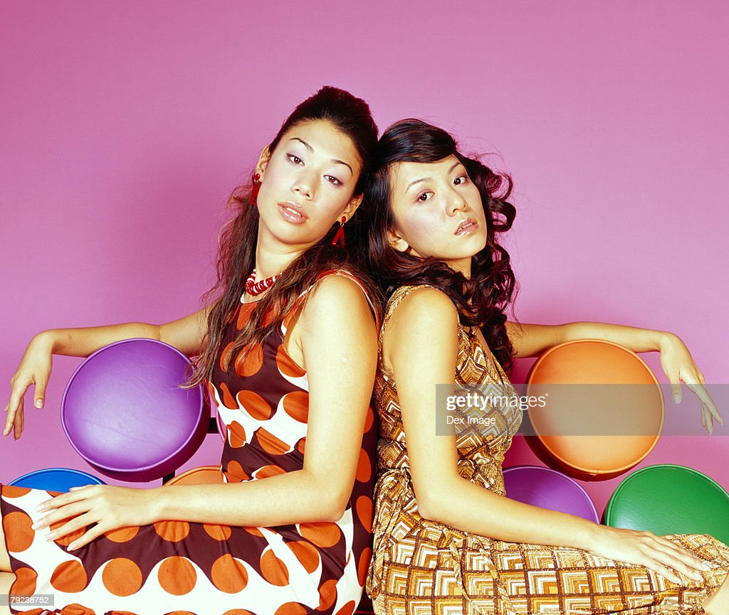Two woman sitting on a colorful sofa : Stock Photo
