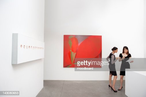 Two woman standing next to wall paintings : Foto de stock