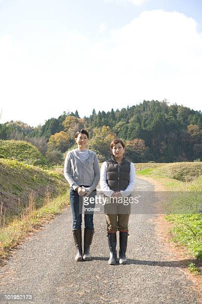 Two woman standing on dirt road, front view