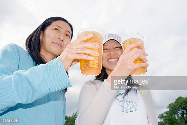 Two woman toasting with beer in plastic cups