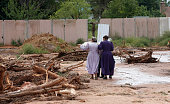 Two woman walk amongst debris left behind after a flash flood on September 15 2015 in Hildale Utah Flash floods from heavy rains on the afternoon of...