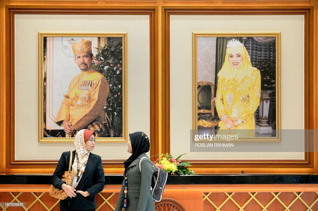 Two woman walk past portraits of Brunei Sultan Hassanal Bolkiah (L) and Queen Saleha (R) at the prime minister's complex in Bandar Seri Begawan on April 24, 2013 ahead of the start of the Association of Southeast Asian Nations (ASEAN) summit. Southeast Asian leaders are meeting in Brunei hoping to heal wounds from infighting over relations with China while building momentum towards groundbreaking economic partnerships. AFP PHOTO / ROSLAN RAHMAN