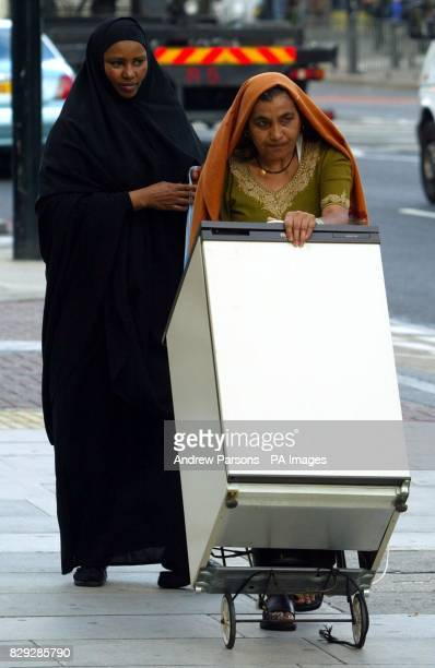 Two woman wheeling a fridge down Bow Rd East London