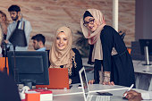 Two woman with hijab working on laptop in office