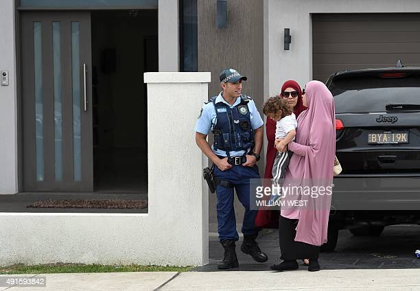 Two women and a child leave a house being searched by police as four people were arrested over the terrorlinked murder of a police employee after...