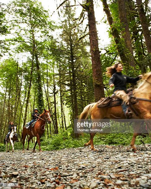 Two women and a girl riding horses on trail.