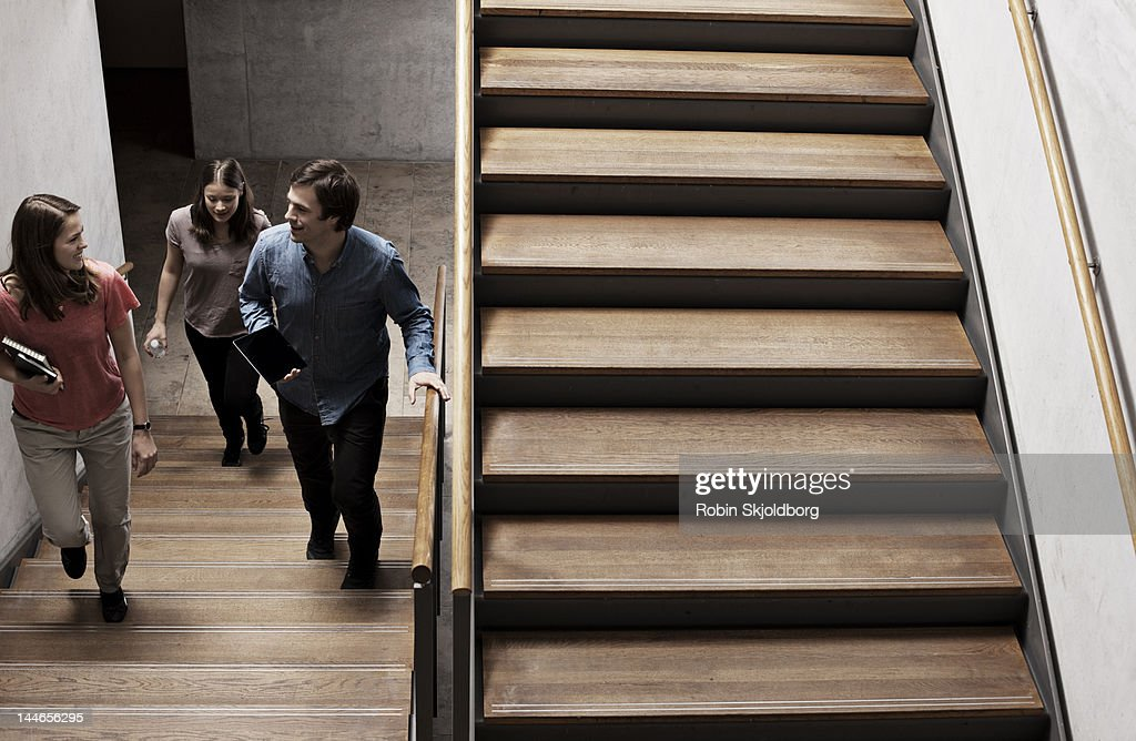 Two women and a man walking on stairs. : Stock Photo