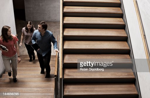 Two women and a man walking on stairs. : Bildbanksbilder