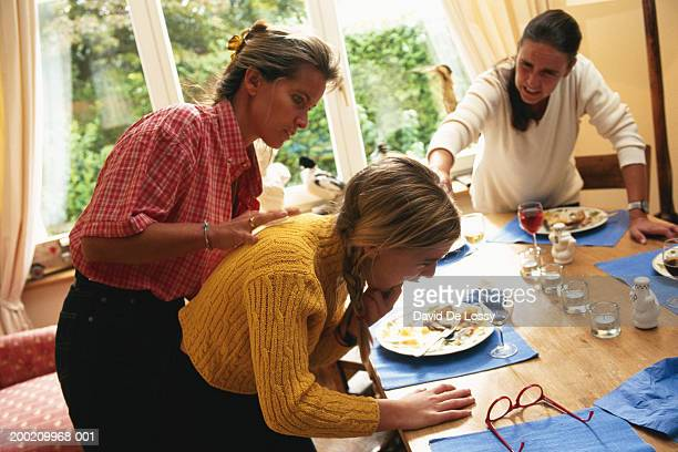 Two women and girl at dinning table