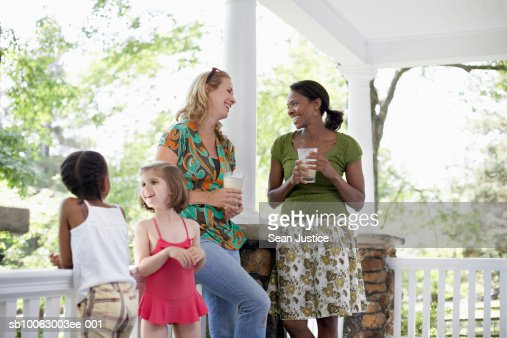 Two women and girls (7-8 years) talking on porch