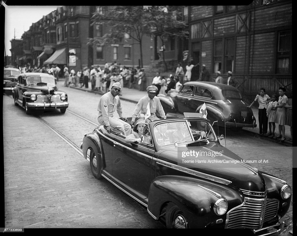 Two women and man seated in front seat of convertible car with two men wearing military uniforms seated in back riding down street in parade with...