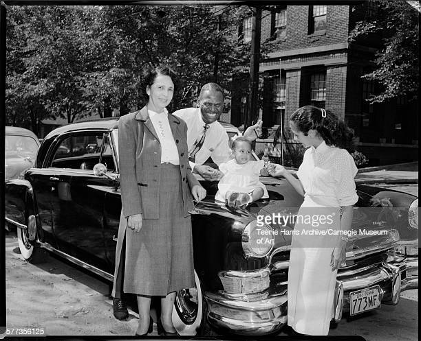 Two women and man standing around baby girl seated on hood of dark Chrysler car with Pennsylvania license plate number '773MF' on Centre Avenue with...