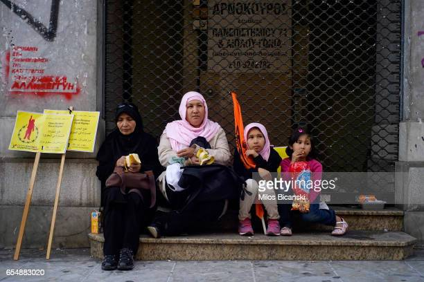 Two women and two young girls rest on a step after taking part in a demonstration by Greek antifascist groups against the war in Syria and the...
