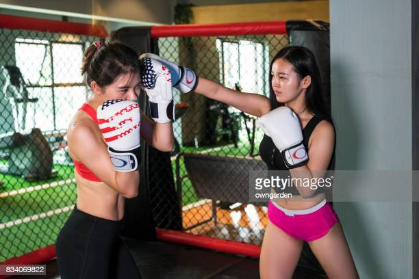 Two women are boxing at the gym