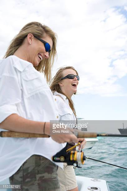 Two women are laughing while fishing off the side of a boat.
