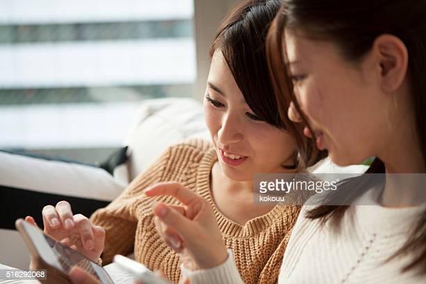 で遊ぶ 2 人の女性がスマートフォンでお部屋