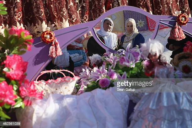 Two women are reflected in a mirror of a bed as they arrive at the house of bride Fatme Inus to see items of her dowry on display outside on the...