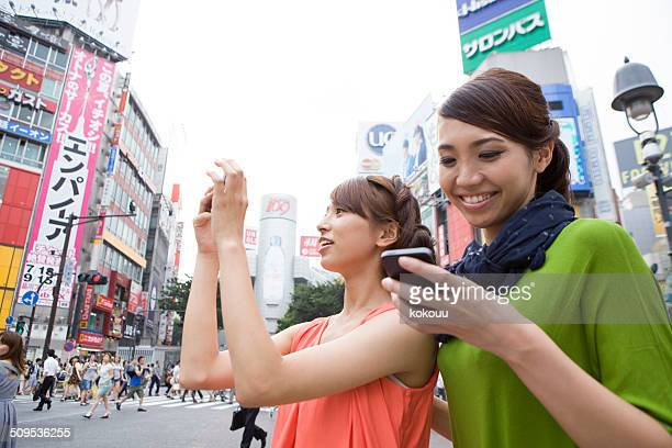 Two women are taking pictures at Shibuya crossing