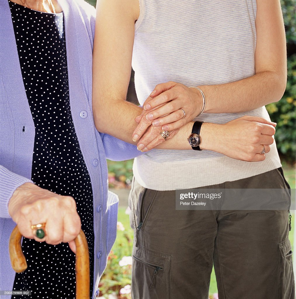 Two women arm in arm, one holding walking stick, mid section, close up : Stock Photo