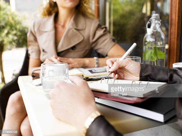 Two women at an outdoor restaurant with a day planner