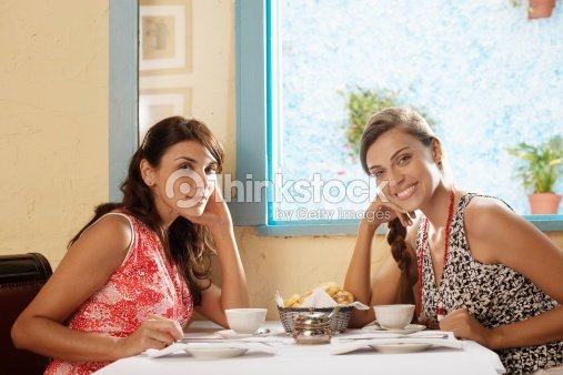 Two women at dining table in restaurant (portrait)   Stock Photo 8e144a8aa