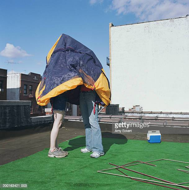 Two women attempting to put up tent on rooftop