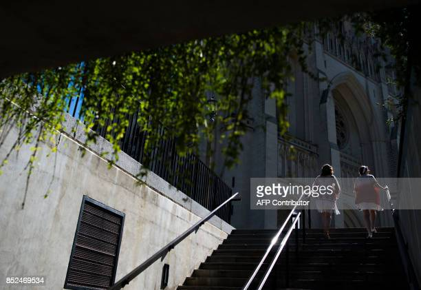 Two women attending Dardanella a Great Gatsby Lawn party walk up stairs to the National Cathedral in Washington DC on September 23 2017 'Dardanella'...