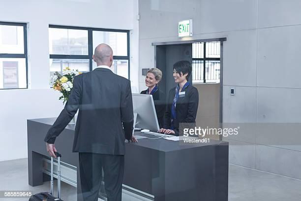 Two women behind reception desk in hotel lobby helping businessman