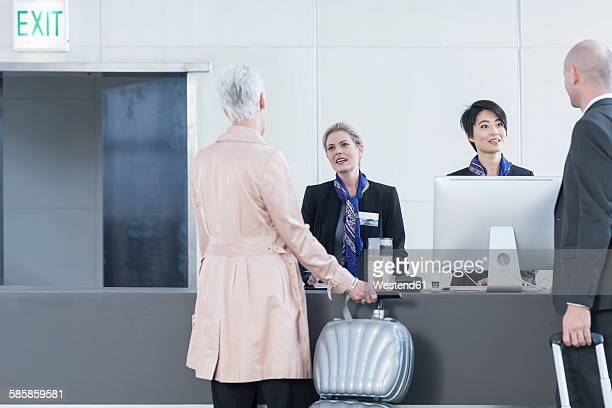 Two women behind reception desk in hotel lobby helping guests
