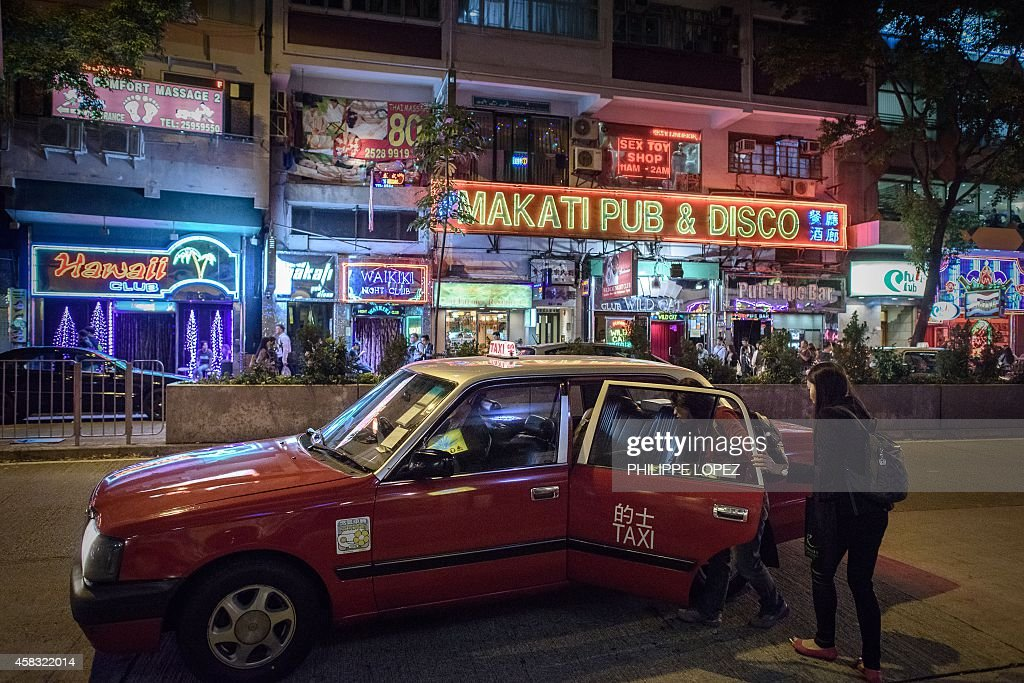 Two women board a taxi near bars and restaurants in Hong Kong's Wanchai district on November 3 2014 A British banker appeared in a Hong Kong court on...