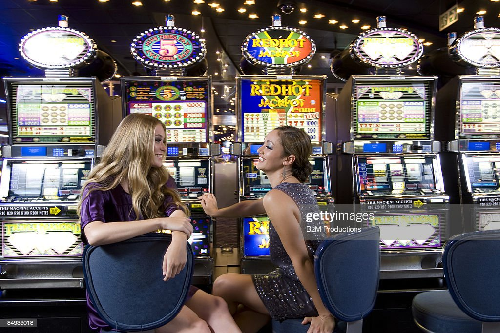 Two women  by slot machines in casino, smiling : Stock Photo