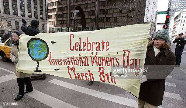 Two women carry a banner as they march along a street for International Women's Day March 8 2005 in Chicago Illinois Women and their supporters...