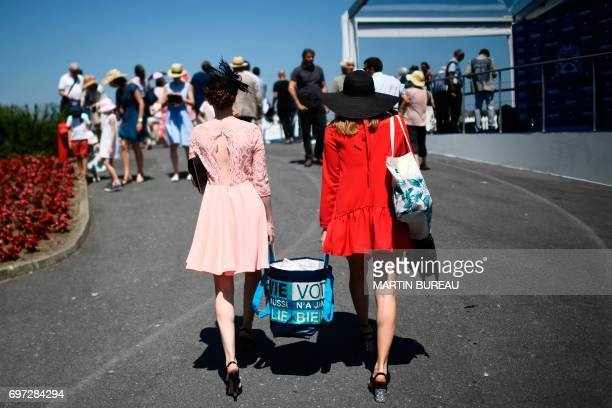 Two women carry a shopping bag as they arrive prior to the start of the Prix de Diane a 2100meters flat horse race on June 18 2017 at the Chantilly...