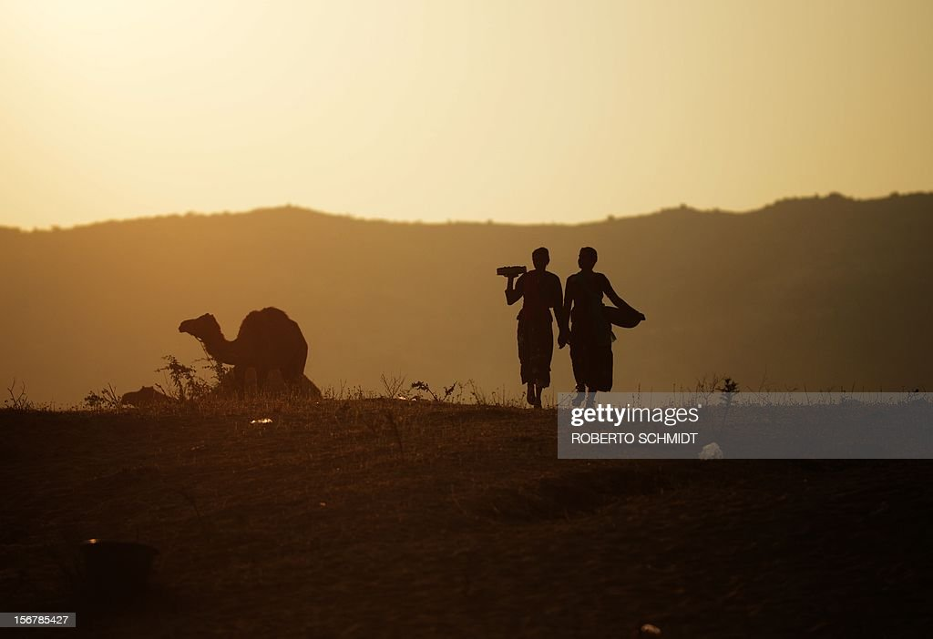 Two women carry camel dung they collected in a dusty field during sunrise at the camel fair grounds in the outskirts of Pushkar on November 21, 2012. The annual five-day camel and livestock fair, held in the town of Pushkar in the state of Rajasthan is one of the world's largest camel fairs, and apart from buying and selling of livestock it has become an important tourist attraction. AFP PHOTO/Roberto Schmidt