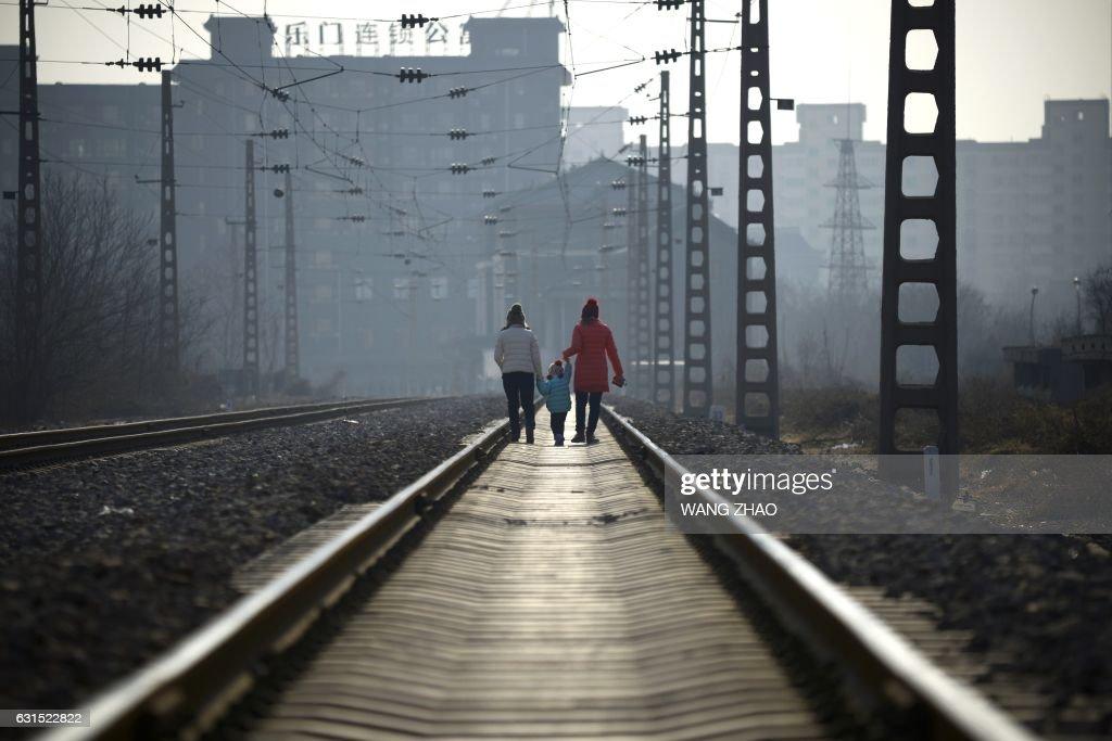 TOPSHOT - Two women carrying a child walk along a railway in Beijing on January 12, 2017. /