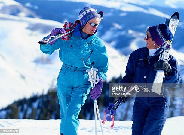 Two Women Carrying Their Downhill Skis