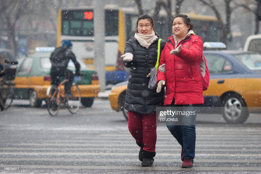 Two women catch snowflakes as they cross a road in Beijing on December 12, 2012. Snowfall hit the Chinese capital with seasonal minus temperatures forecast to bring more later in the week. AFP PHOTO / Ed Jones