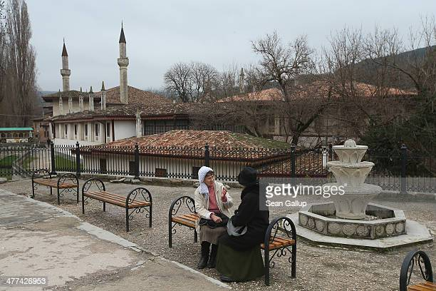 Two women chat next to a fountain next to the Khan's Palace also called Hansaray in Crimea on March 9 2014 in Bakhchysarai Ukraine Bakhchysarai was...