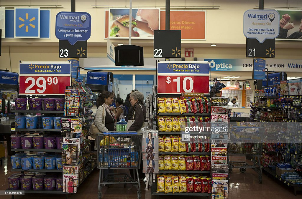 Two women chat while waiting in the checkout line at a Wal-Mart Stores Inc. location in Mexico City, Mexico, on Thursday, June 20, 2013. Mexican retail sales rose 2.5 percent in April from the same month last year, the country's statistics agency, known as Inegi, reported on its website. Photographer: Susana Gonzalez/Bloomberg via Getty Images
