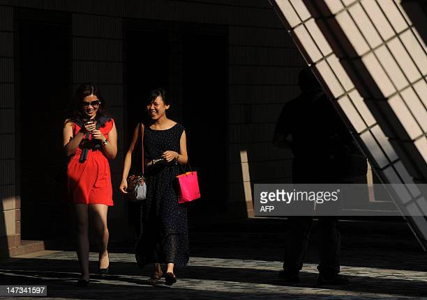 Two women chat while walking along a path in Hong Kong on June 28 2012 Hong Kong is facing 'unprecedented challenges' amid the global economic crisis...