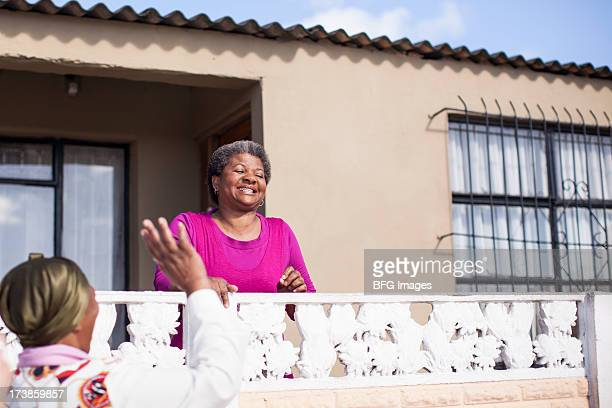 Two women chatting over a fence, Cape Town, South Afric