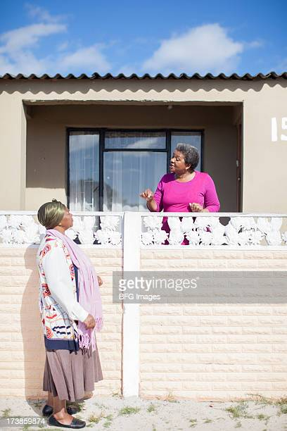 Two women chatting over a fence, Cape Town, South Africa
