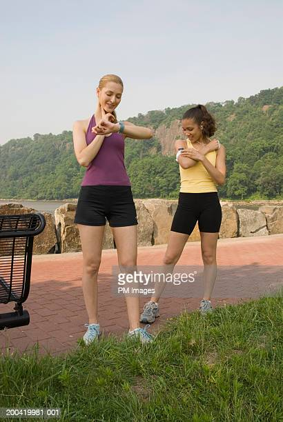 Two women checking pulse and listening to music player