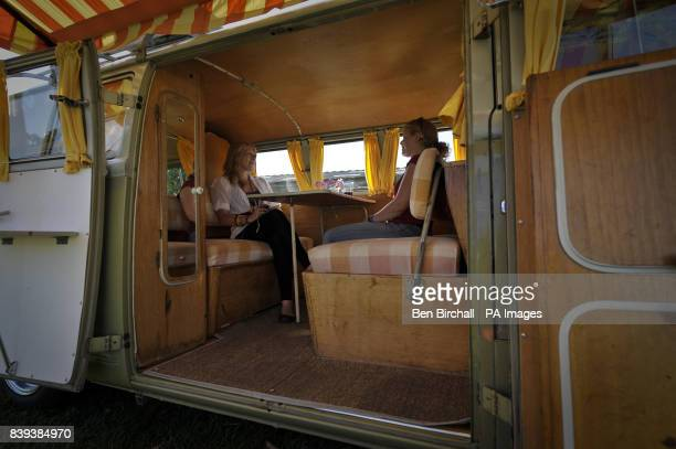 Two women chill out in their 'Mosaic' converted interior 1960's VW Splitscreen Type 2 Transporter at Vanfest festival in the Three Counties...