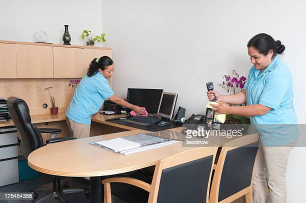 Two women cleaning the inside of an office