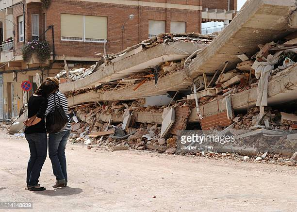 Two women comfort eachother at the sight of a collapsed building on May 13 2011 in Lorca Spain Nine people where killed in the earthquakes measuring...