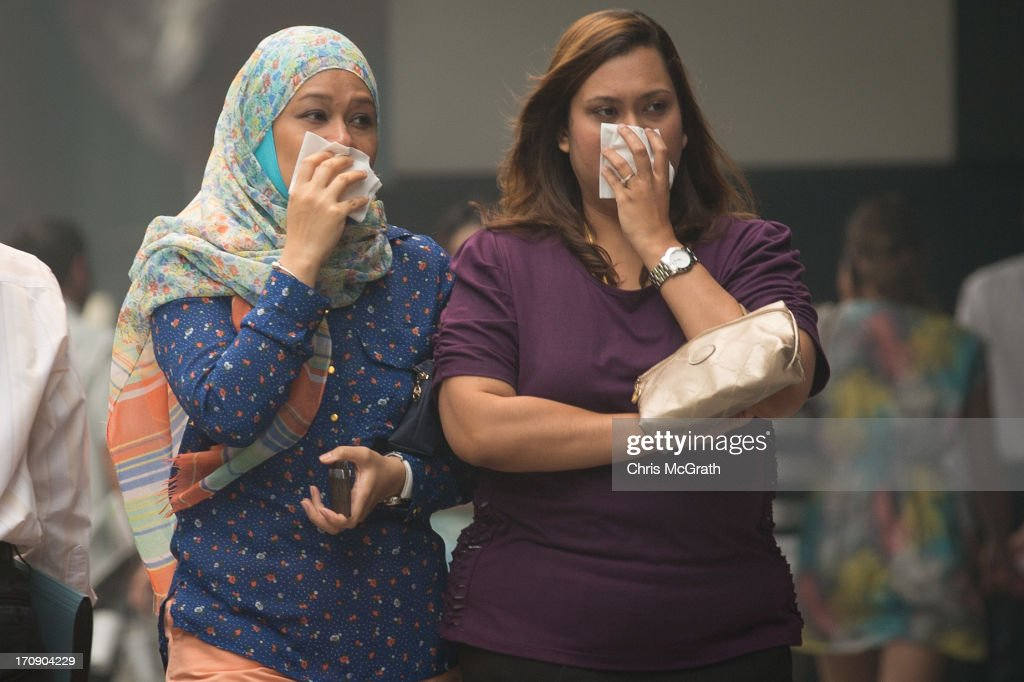 Two women cover their face with tissues as they walk through Raffles Place in the central business district on June 20, 2013 in Singapore. The Pollutant Standards Index (PSI) rose to the highest level on record reaching 371 at 1pm. The haze is created by deliberate slash-and-burn forest fires started by companies in neighbouring Sumatra.