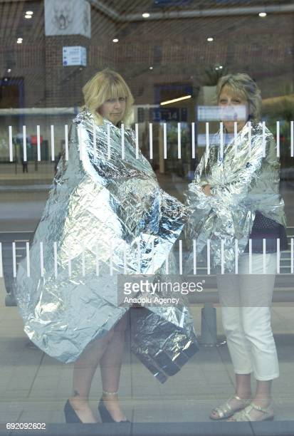 Two women cover themselves with thermal blankets inside London Bridge Station while police officers search the area around Borough Market central...